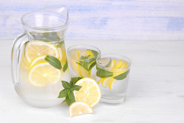 Homemade lemonade with lemon and mint in a glass jug and a glass next to fresh lemon on a white and blue wooden background...