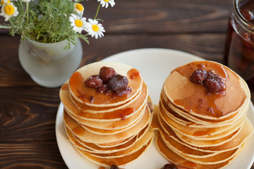 Pancakes with strawberry jam for a breakfast on a kitchen table. Sweet food and good mood