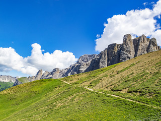 Picturesque diagonal Alpine view from the Sella Pass in the Dolomites with big cumulus clouds, South Tyrol, Italy
