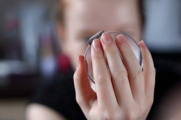 Fototapeta Dłoń młodziutkiej dziewczyny trzyma lusterko, w nim przegląda się  ta dziewczynka, twarz rozmyta, rozmyte tło