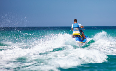 young adult man running the wave on jet ski during summer vacation