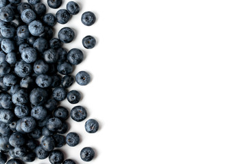 Blueberries scattered on a white background, top view.