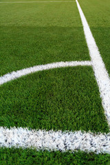 The angle of the football field. White marking applied on a green synthetic lawn of a football field.