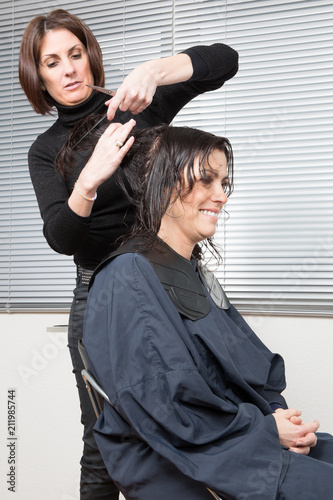 Hairdresser Makes Hairstyle For Middle Aged Woman In Beauty Salon