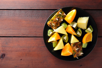 Fruit salad for vegans, pieces of pineapple, oranges and kiwi on a black plate, tropical fruits on wooden boards, citrus salad top view, copy space