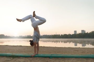 Young athletic man doing yoga poses near the lacke
