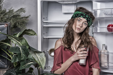 Woman with tired look standing next to open fridge. Girl holding glass of milk. Lady with curly hair and green headband in kitchen, food and diet concept. Big green plant in dining room interior