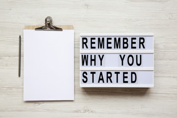 'Remember why you started' words on lightbox, noticeboard, pencil over white wooden background, from above. Top view, flat lay, overhead.