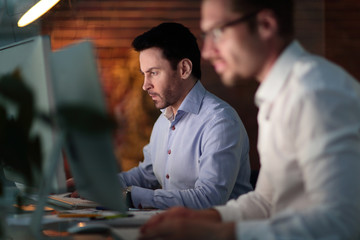 Businesspeople in the office at night working late