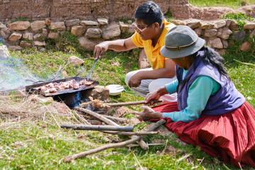 Native american people cooking meat in the countryside.