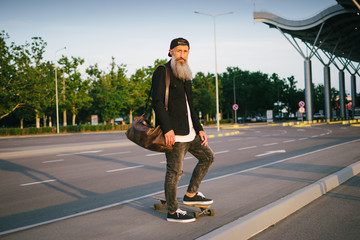 Stylish handsome middle-aged man with long gray beard standing with longboard on urban background