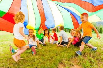 Cheerful kids hiding under rainbow canopy