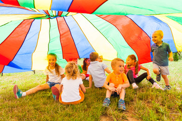 Laughing kids hide in multicolor shelter