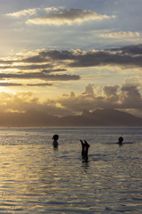 Swimmers at Sunset with Moorea in Background