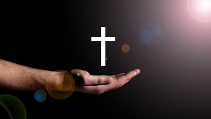Male hand showing the cross, concept of the religion of Christianity