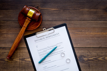Divorce court case. Divorce agreement near wedding rings and judge gavel on dark wooden background top view copy space
