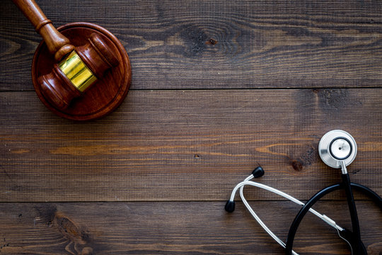 Medical law, health law concept. Gavel and stethoscope on dark wooden backgound top view copy space