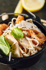 Noodles with Shrimps, Chicken, in Metal Bowler with Sesame Seeds on Natural Dark Stone Background