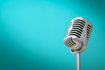 Retro style microphone on green wall background with light comes to the left
