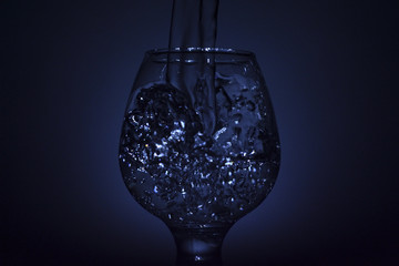 Simple still-life photo of whisky glass, water jet and dim colour light