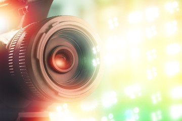 lens of TV camera in stadium with light background during sports match