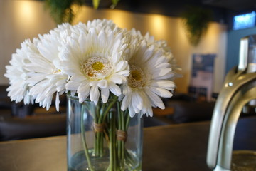 Beautiful flowers are arranged on the dinner table, decoration interior design concept in restaurant and cafe