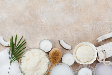 Spa setting from body care, wellness and beauty treatment. Coconut scrub, oil and cream on stone table top view. Flat lay.