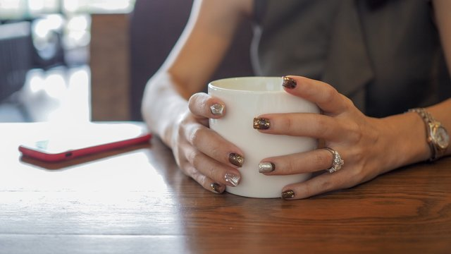 Closeup of woman's hands with coffee cup and smartphone