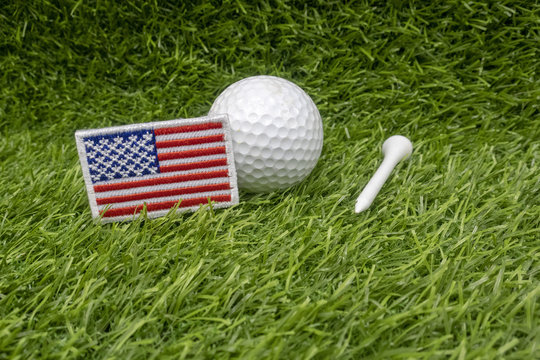 Golf ball with American flag is on green grass