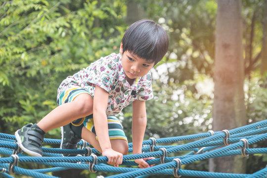 Asian boy is climbing on rope bridge in playground