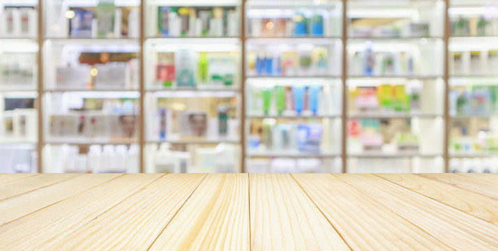 Pharmacy wood table counter with medicines healthcare product arranged on shelves in drugstore blurred defocused background