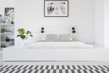 Real photo of a king-size platform bed standing in a white bedroom interior with a patterned rug and shelves in the bacground