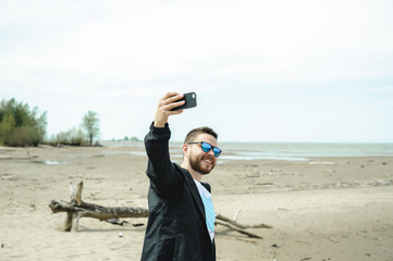young bearded man, dressed in youth clothes, travels by the sea, adventures on a warm summer day.