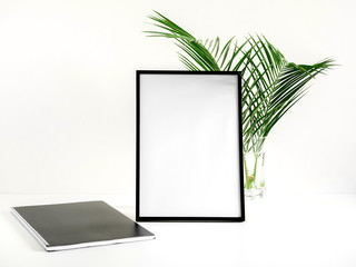Front view blank mock up of photo frame on white background, notebook, green plant. Flat lay, top view, copy space