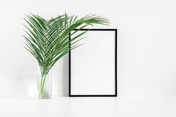 Front view blank mock up of photo frame on white background, tropical palm leaves. Summer concept. Flat lay, top view, copy space