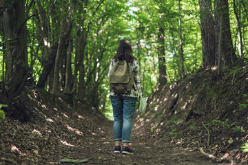 Young woman with backpack explores map on forest path. Woman with tourist backpack travels