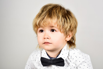 Cute little boy in fashionable shirt and bow tie. Sad little boy, portrait. Stylish kid in elegant wear. Children fashion. Fashion for kids. Feelings and emotions. Child with sad expression on face.