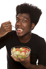 young handsome afro american guy eat salad isolated on white background. healthy food concept