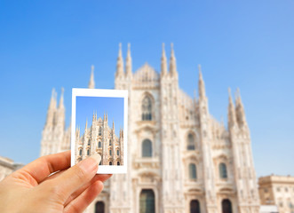 Hand holding Instant photo in Europe Milan Cathedral, Duomo di Milano, Italy, Concept holiday, tourist on vacation background.
