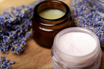 Bunch of lavender and cosmetic pot on a wooden table