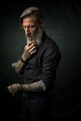 Portrait eines attraktiven bärtigen Mannes mit verschränkten Armen