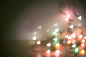 Blur christmas lights with bokeh heart shape light low depth of focus with copy space in concept vintage tone style.