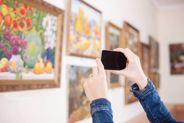 Woman photograph a painting at an exhibition in the art gallery.