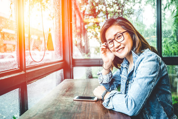 Glasses nerd hipster asian woman sitting smile in glass windows cafe with smartphone