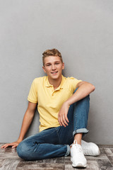 Portrait of a smiling casual teenage boy with sitting