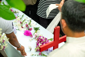 People on funeral Putting Flowers and Earth Soil on Coffin, ASEAN Outdoor Funeral Ceremony.