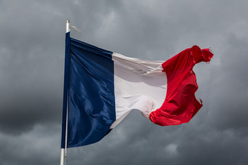 The French national flag against a stormy sky