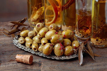 Spiced green olives and bottles with olive oil .