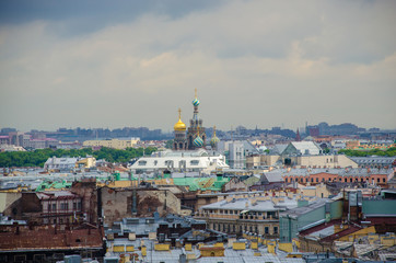 Domes of the Church of the Savior on Blood above the roofs of houses in St. Petersburg