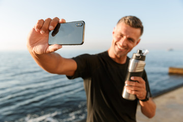 Mature sportsman take a selfie with bottle of water on the beach.